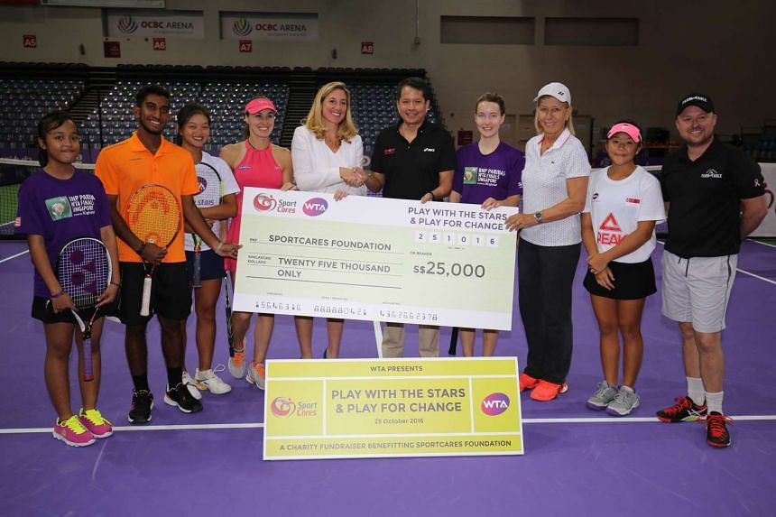 WTA Finals tournament director Melissa Pine presenting S$25,000 to Sport Singapore chairman Richard Seow (fifth from right), along with Martina Hingis (fourth from left) and Martina Navratilova (third from right).