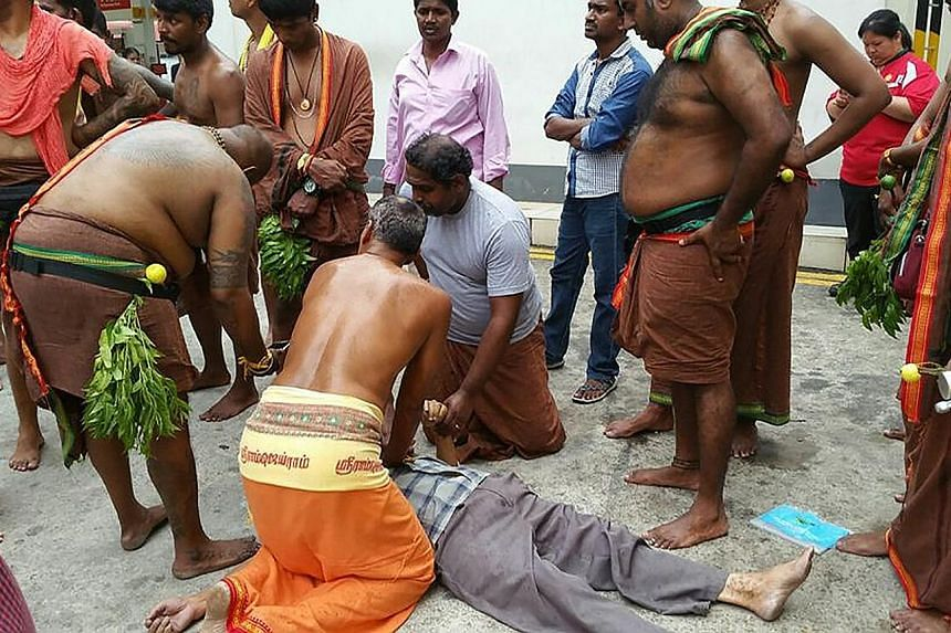 Mr U. Silvakumar (in orange and below right) administering CPR to an elderly Chinese man on Sunday. With him are other Hindu devotees who helped the unconscious man. Photos of the incident have gone viral and the men's actions have drawn praise.