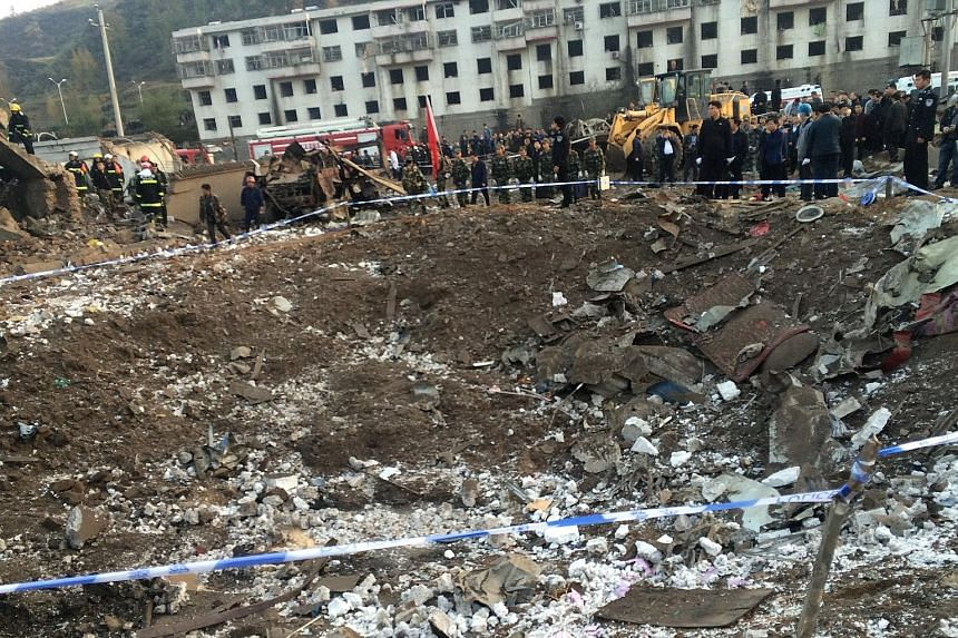 Rescue workers at the site of a blast in the town of Xinmin in Fugu county, Shaanxi province, yesterday. The explosion in a prefabricated house reportedly left a 5m-wide and 4m-deep crater next to a hospital, part of which was blown off. Other buildi