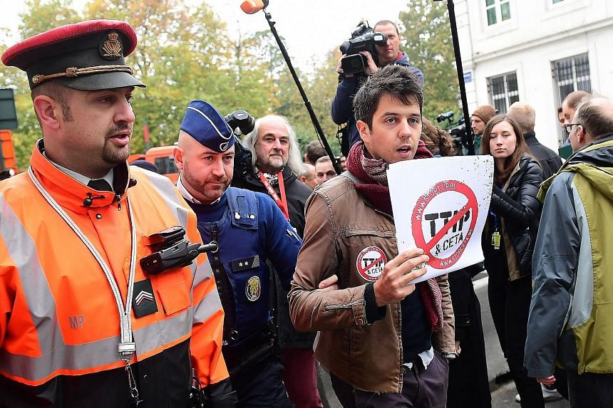 A demonstrator being led away by police ahead of the emergency meeting of Belgian federal entities in Brussels yesterday. The small Belgian region of Wallonia has set back the trade deal with Canada that all 27 other EU member states were ready to su