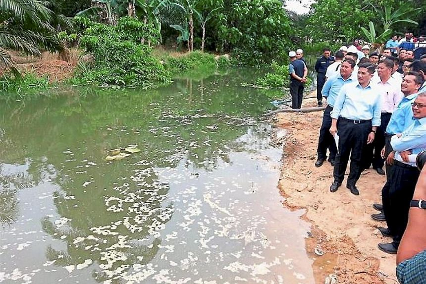 Mentri Besar Mohamad Azmin Ali (front row, third from right) checking the contaminated water at Sungai Buah after workers blocked it from flowing into Sungai Semenyih.