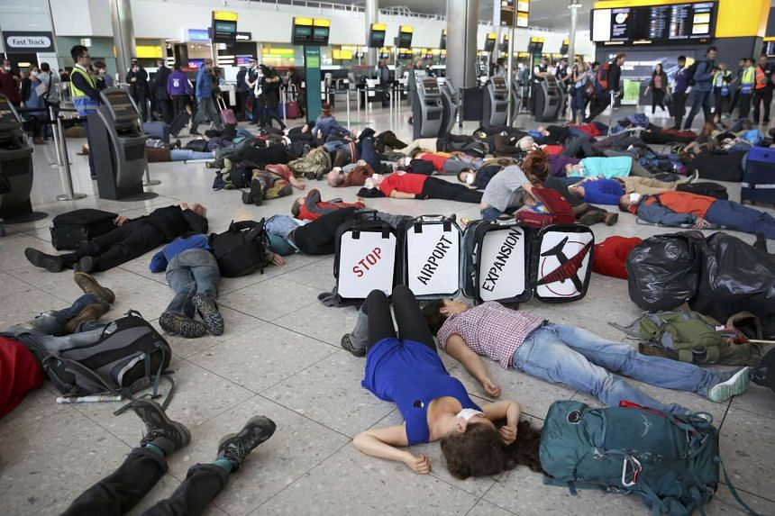 Climate activist group Reclaim the Power lie on the ground and carry luggage during a protest against airport expansion plans at Heathrow Airport in London, Britain on October 1, 2016