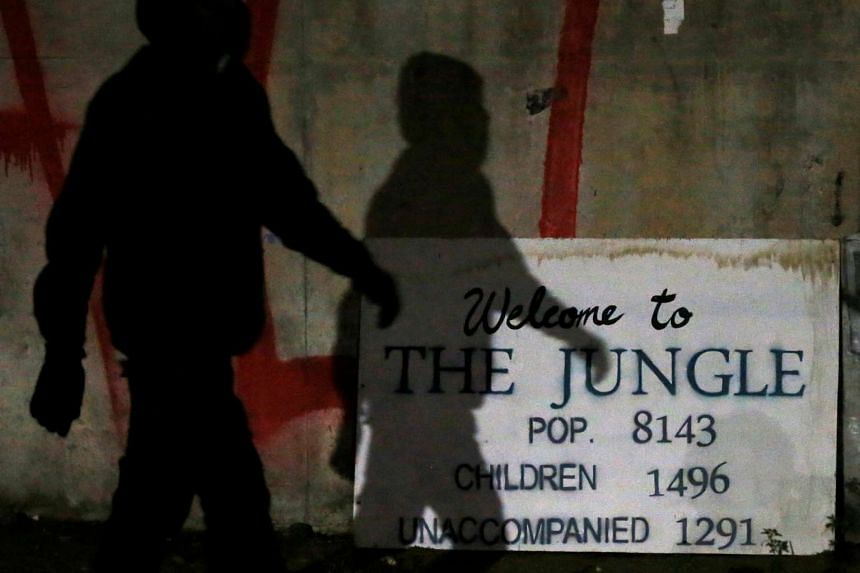 The shadow of a migrant falls on a sign with the population of The Jungle at the end of the first day of the evacuation.