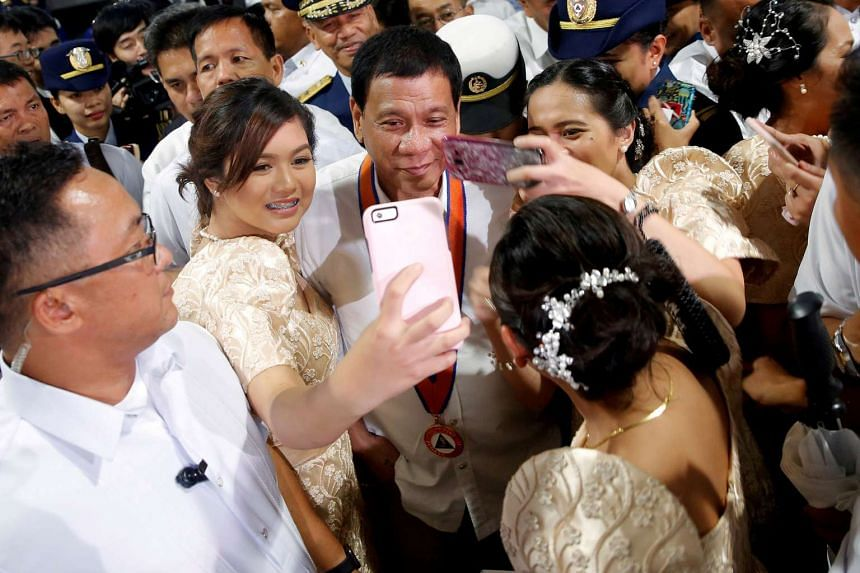 Philippines President Rodrigo Duterte taking a picture with the public as he attends a ceremony marking the anniversary of the Philippines Coast Guard in Manila.