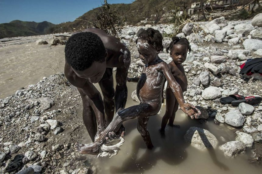 A man bathes his daughters in a river, which could be contaminated with cholera, in Rendel, Haiti.