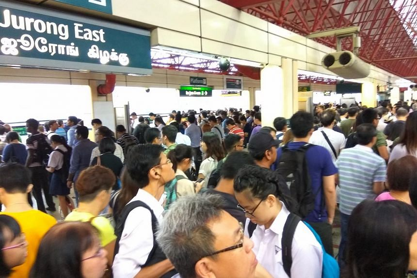 Commuters on the crowded train platform at Jurong East MRT station.