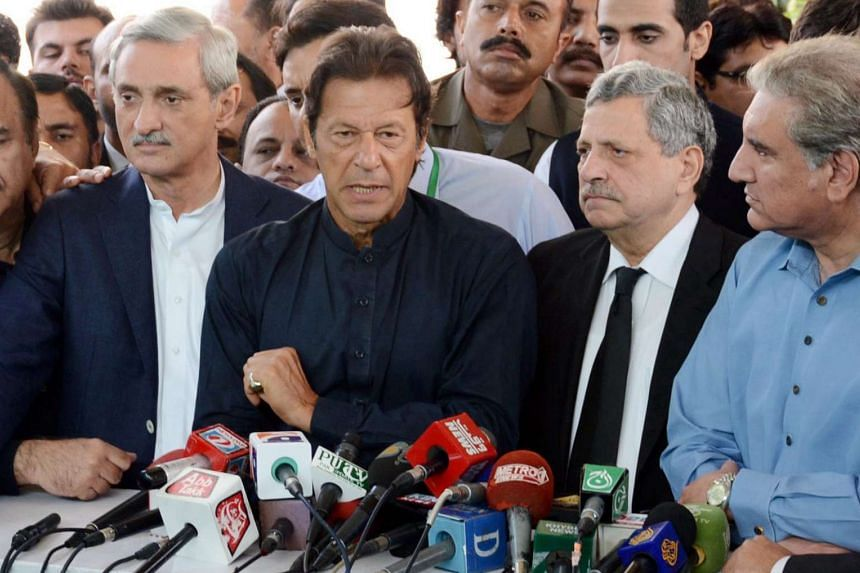 Imran Khan (centre), the head of opposition political party Pakistan Tehrik-e-Insaf (PTI), stands with his party leaders Jahangir Tareen (left), Hamid Khan (second from right) and Shah Mehmood Qureshi during a press conference in Islamabad, Pakistan