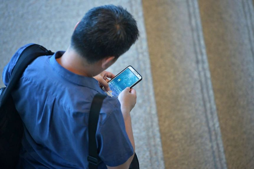 An office worker using his mobile phone at Raffles Place.