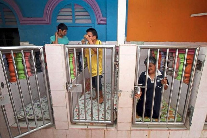 "Residents at the Handicapped Children's Welfare Home getting ready for bedtime in their ""special cubicles""."