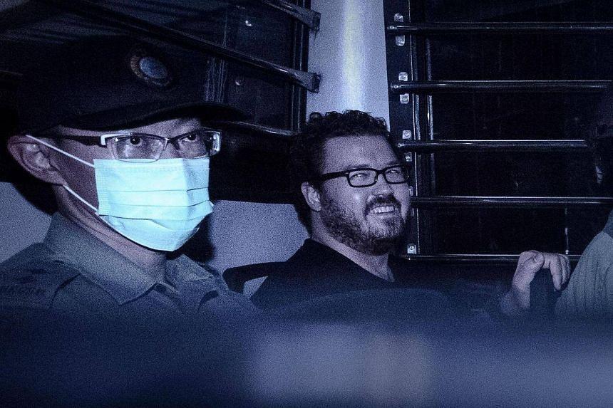 This file photo taken on Nov 10, 2014 shows British banker Rurik Jutting (right) smiling as he sits in a prison van.