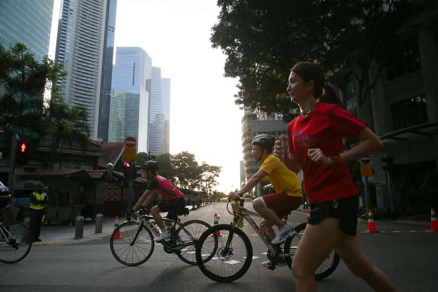 Joggers and cyclists take to the streets along Shenton Way on Car-Free Sunday on Feb 28, 2016.