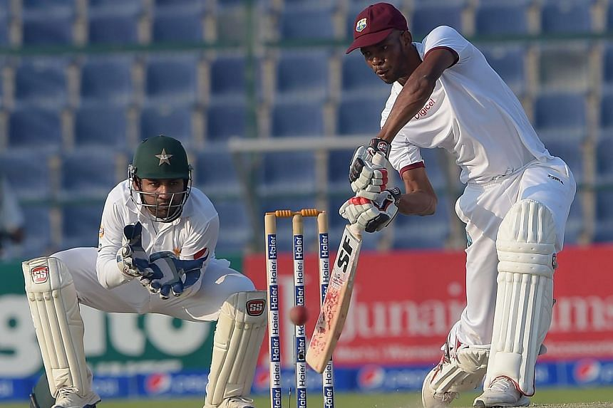 The West Indies' batsman Roston Chase (right) plays a shot as Pakistani wicketkeeper Sarfraz Ahmed looks on during the fourth day of the second Test between Pakistan and the West Indies.