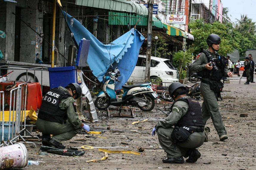 A Thai bomb squad inspects the site of a deadly bombing from the night before outside of a hotel, in the southern province of Pattani on August 24, 2016. Thailand's insurgency-plagued southern region has seen near daily bombings and shootings since