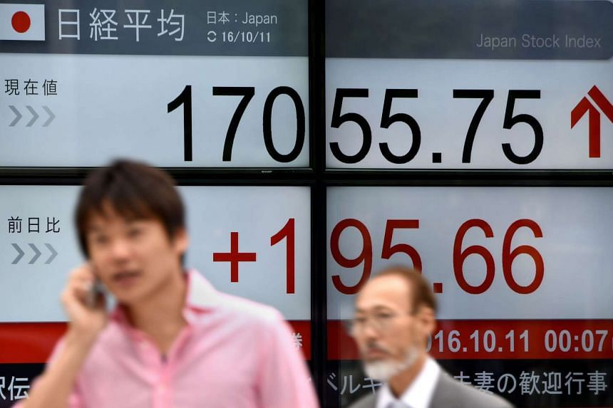 People walk past an electric quotation board flashing the Nikkei key index of the Tokyo Stock Exchange (TSE) in front of a securities company in Tokyo on Oct 11, 2016.