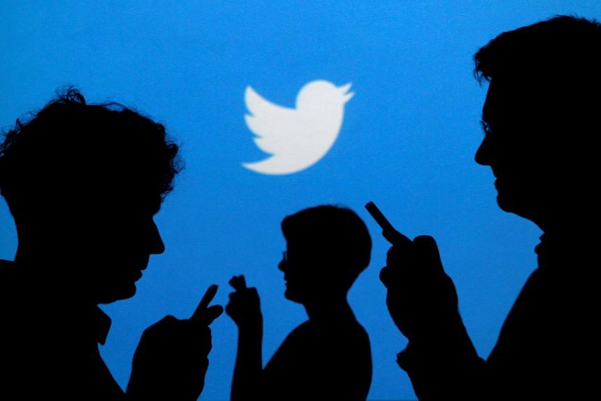 People silhouetted against a backdrop with the Twitter logo.