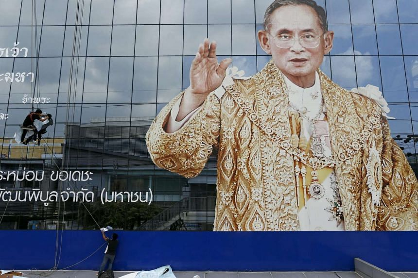 Thai workers install remembrance mourning message next to a portrait of late Thai King Bhumibol Adulyadej at a company building in Bangkok on Oct 24, 2016.