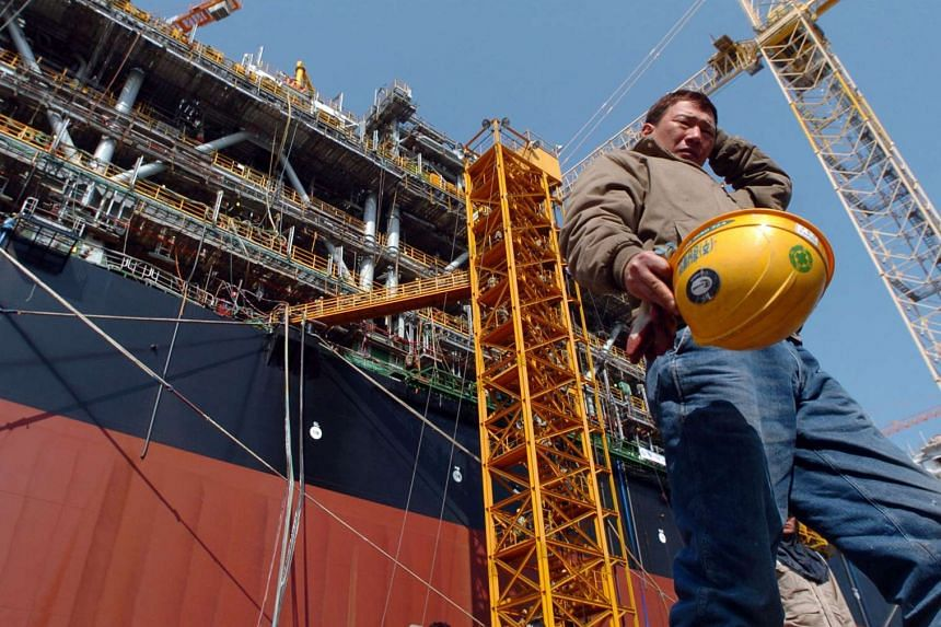 An employee of Daewoo Shipbuilding & Marine Engineering Co. walks past a ship being constructed at the company's shipyards in Geoje Island, South Korea.