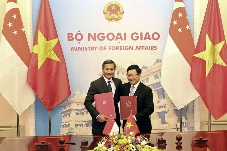 Singapore's Minister of Foreign Affairs, Vivian Balakrishnan (left) and his Vietnamese counterpart Pham Binh Minh pose for a photo after a signing ceremony at the Government Guest House in Hanoi on Oct 26, 2016.