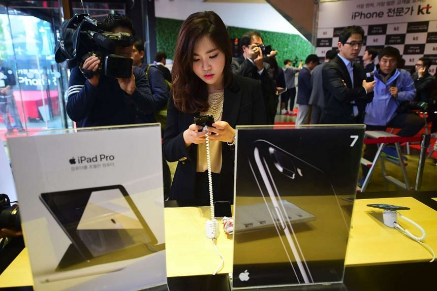 A woman looks at the Apple iPhone 7 at a telecom shop in Seoul on Oct 21, 2016.