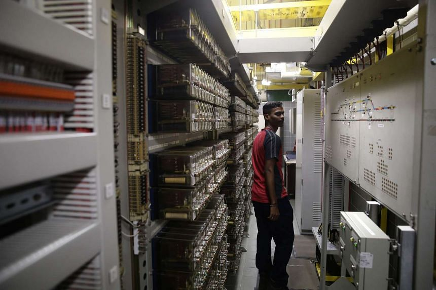 A staff walks past the existing relays (left) and station control panel (right), both of which will be replaced, in the signalling equipment room of Woodlands MRT station.