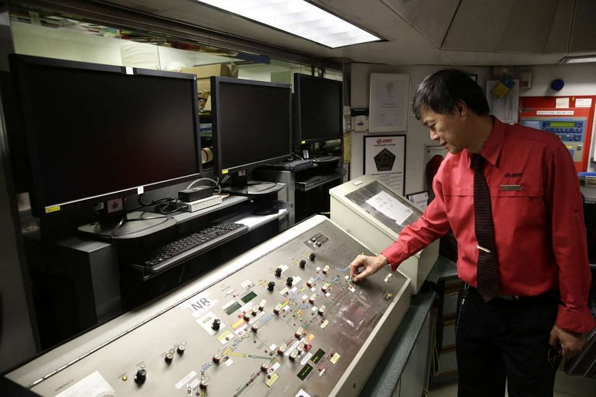 An SMRT staff showing the existing station control panel, which will be replaced by computer screens (above) that shows the location of trains, in the station control of Woodlands MRT station on Oct 26, 2016.