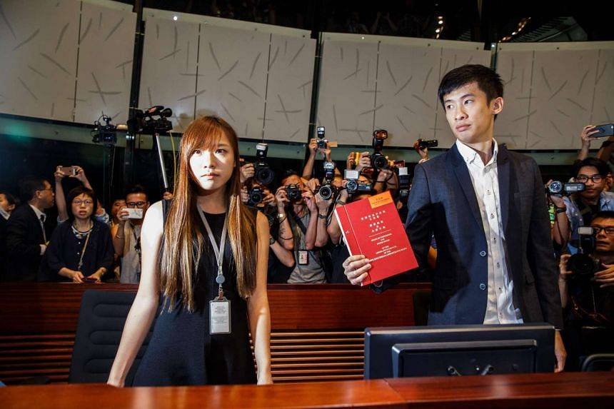 Newly-elected lawmaker Baggio Leung Chung-hang (right) holds up a Legislative Council book next to fellow pro-independence lawmaker Yau Wai-ching while being surrounded by the press.