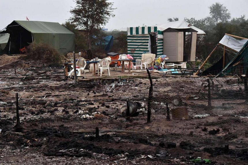 "The remains of a shack set at the ""Jungle"" migrant camp in Calais are seen on Oct 26, 2016, following a fire during the demolition of the camp."