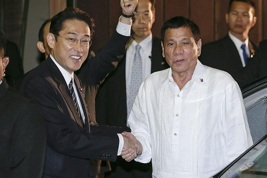 Japanese Foreign Minister Fumio Kishida (left) welcoming Philippine President Rodrigo Duterte to a dinner yesterday at a restaurant in Tokyo. Mr Duterte has arrived in Japan for an official three-day visit.