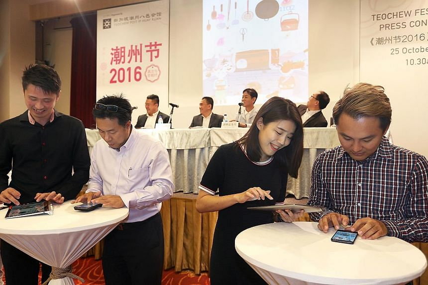 "Left: Guests at the Teochew Festival being briefed on a mobile game centred on the community's culture. Above: Example of a ""qiaopi""."