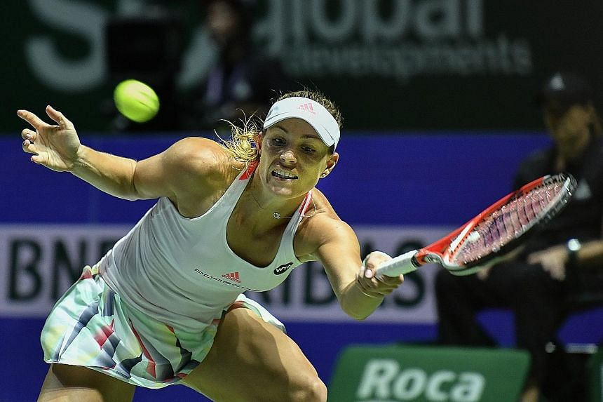 World No. 1 Angelique Kerber at full stretch to retrieve a forehand during her 6-4, 6-2 victory against Simona Halep last night. The German is on the brink of the semi-final stage of the WTA Finals for the first time.