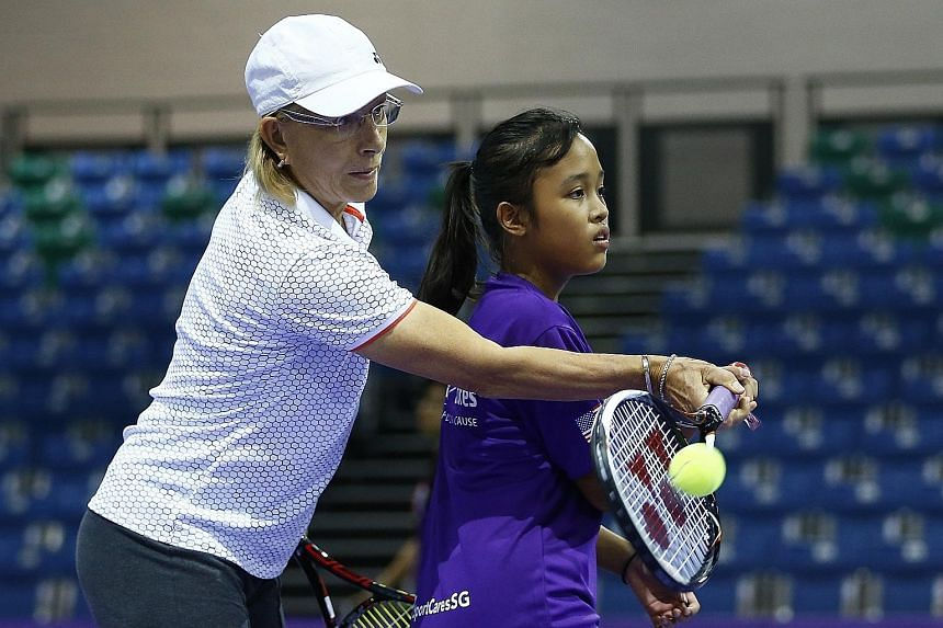 """Retired tennis legend Martina Navratilova guides Naval Base Secondary School student Nur Nabila Malek, 13, on how to hit a forehand at a charity fund-raiser yesterday. Swiss doubles tennis player Martina Hingis was also present at the event, called """""""