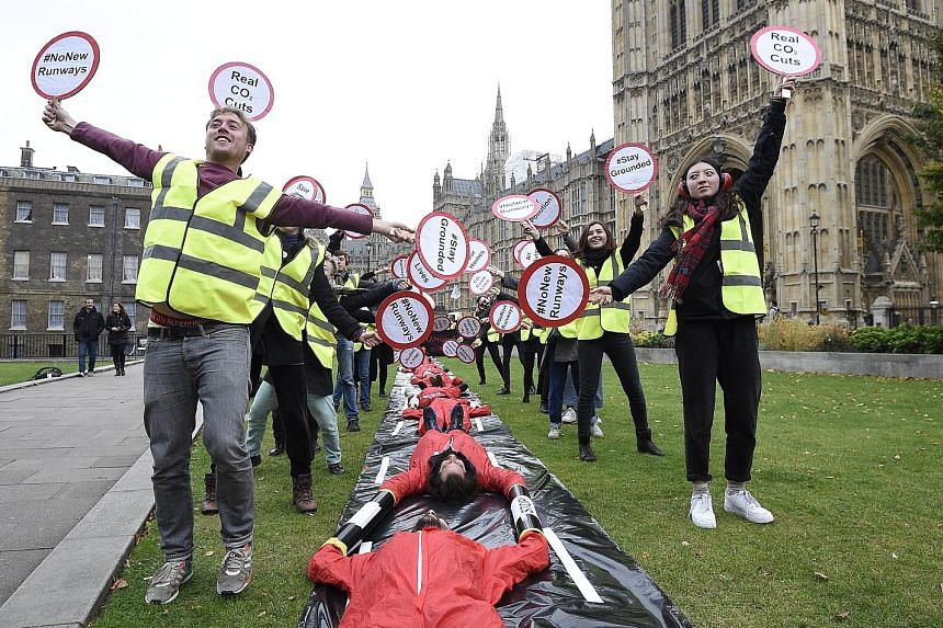 Protesters from Plane Stupid demonstrating outside the Houses of Parliament in London yesterday. According to a study, a new runway at Heathrow would create 70,000 jobs. However, residents are worried about demolition of several villages as well as a