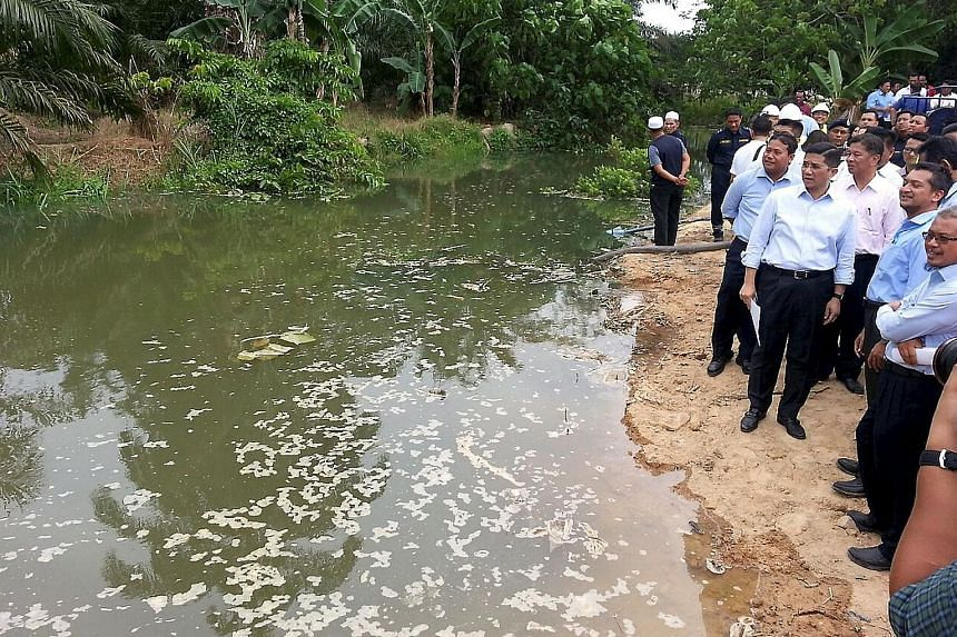 Selangor Menteri Besar Azmin (front row, third from right) in front of the contaminated Sungai Buah. A bund was built across the river to stop the water from flowing into Sungai Semenyih.