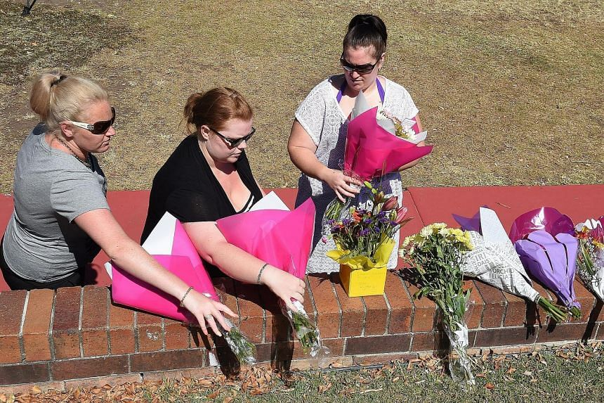 Women lay flowers outside the Dreamworld Theme Park on the Gold Coast, Queensland on Oct 26, 2016.