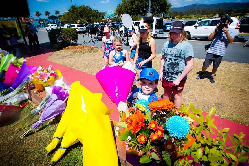 Members of the public lay flowers at a makeshift floral tribute at the Dreamworld theme park on the Gold Coast on Oct 26, 2016.