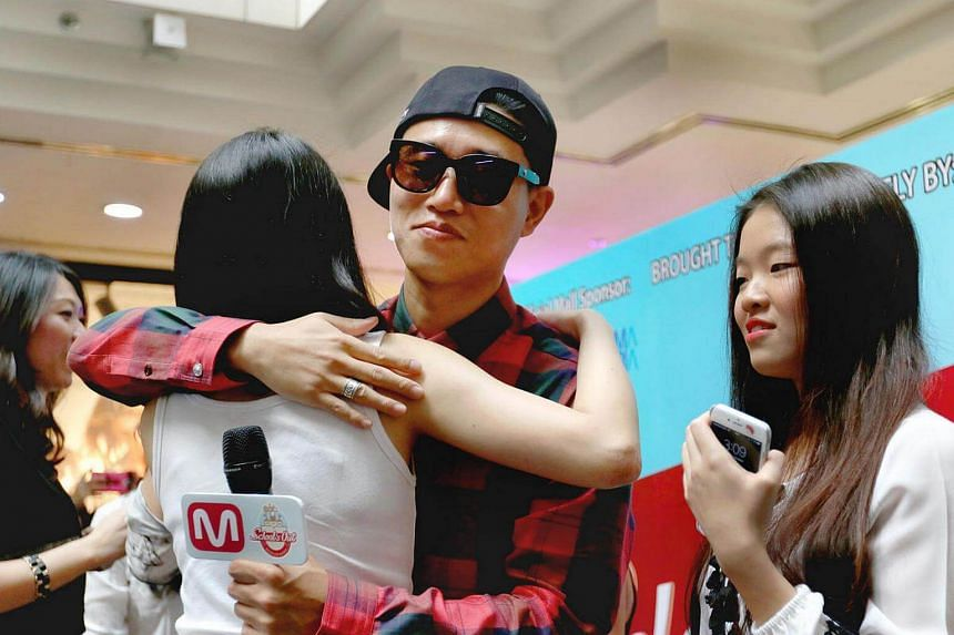 Gary Kang hugging one of his fans during a fan-meet session at Wisma Atria mall on Oct 2, 2015.