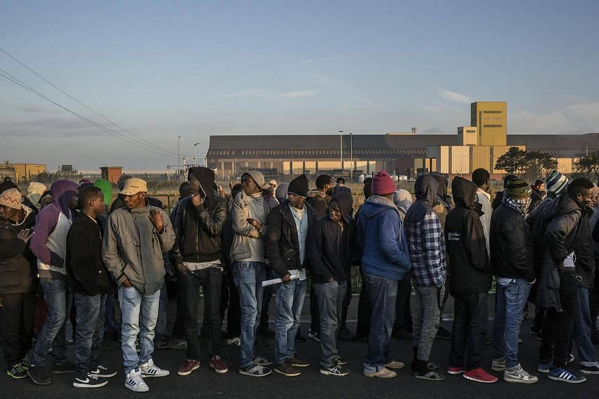Migrants wait outside a reception centre to be registered.