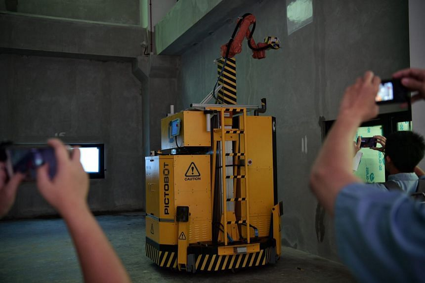 NTU's PictoBot can spray paint high interior walls 25 per cent faster than two humans.