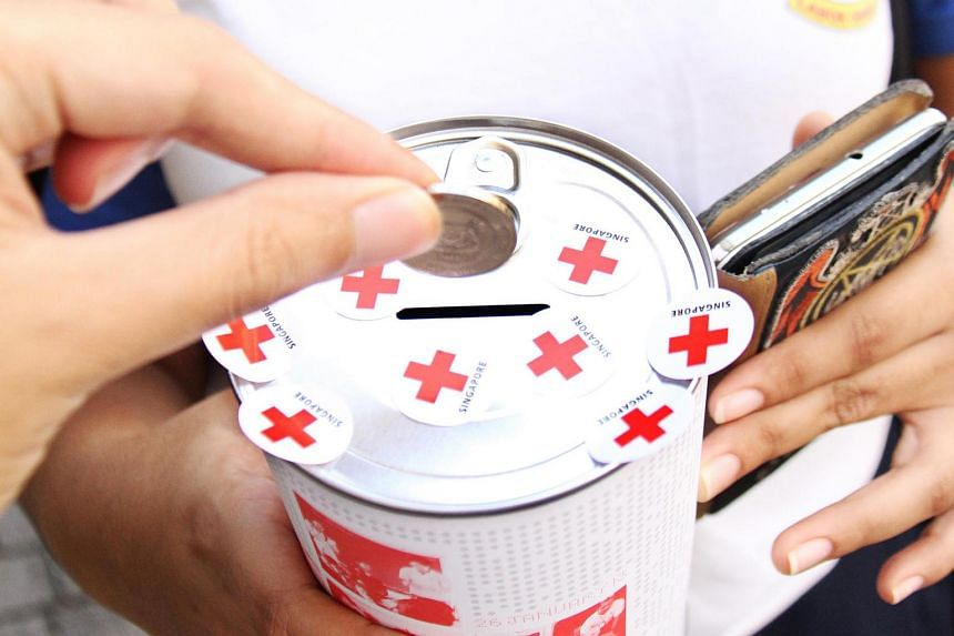 A person putting a coin into a Singapore Red Cross donation tin.