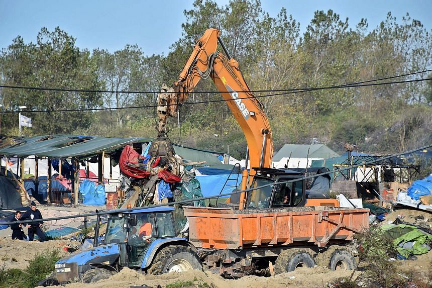 """An excavator tearing down a construction in the """"Jungle"""" migrant camp in Calais, northern France, is pictured on Oct 27, 2016, during a massive operation to clear the squalid settlement."""