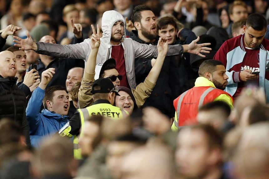 West Ham United's fans gesture towards Chelsea fans during the their League Cup football match.