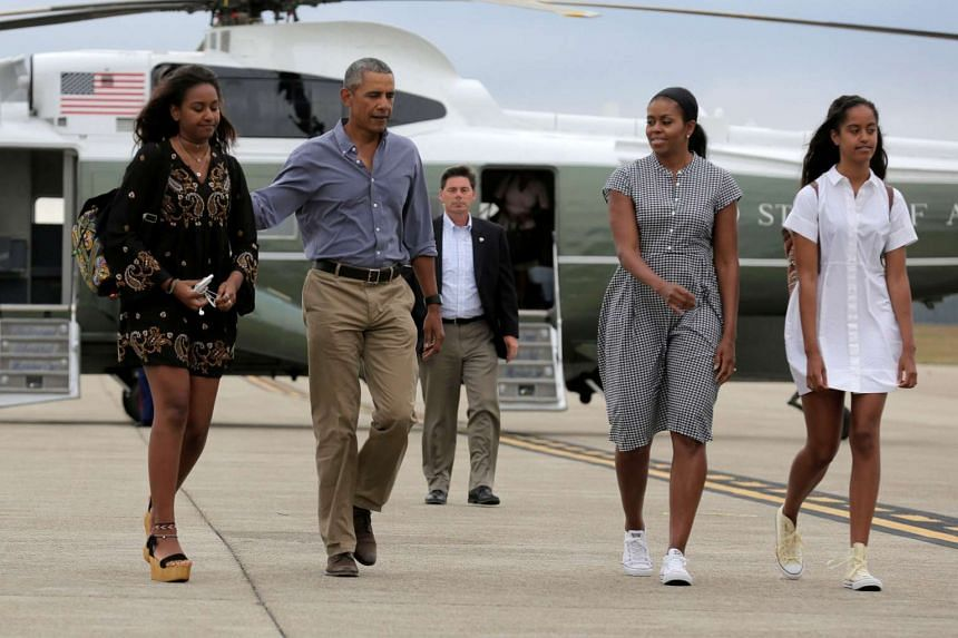 US President Barack Obama,first lady Michelle Obama and their daughters Malia (right) and Sasha (left) board Air Force One at Cape Cod Coast Guard Air Station in Buzzards Bay, Massachusetts on Aug 21, 2016.