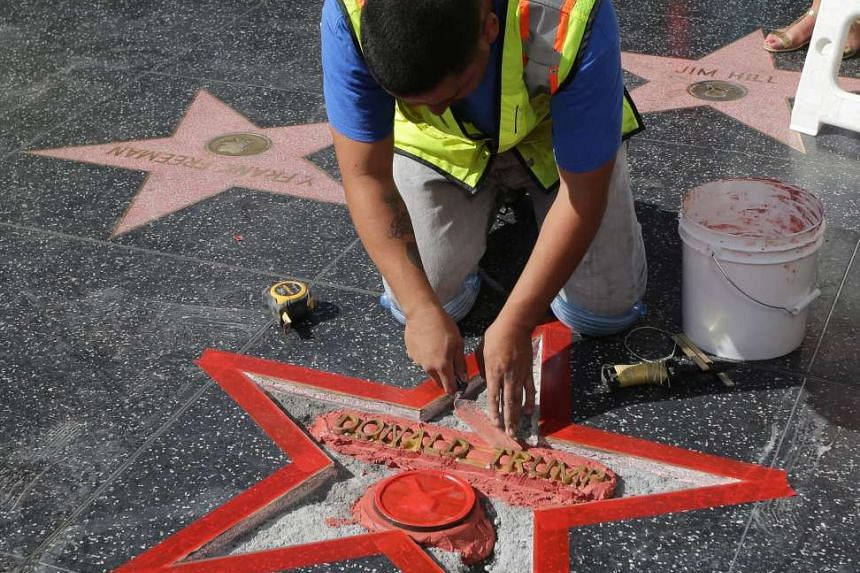 A worker from Top End Constructors repairs US Republican Presidential candidate Donald Trump's star on the Hollywood Walk of Fame after it was destroyed in Hollywood, California, USA on Oct 26, 2016.