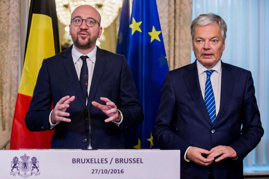 Belgian Prime Minister, Charles Michel (left) and Belgian Foreign Affairs Minister Didier Reynders (right) give a statement after an agreement was reached at the end of the Concertation Committee of Belgium in Brussels, Belgium on Oct 27, 2016. An ag