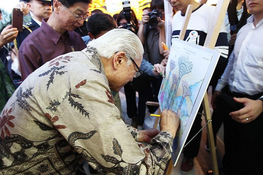 President Tony Tan Keng Yam putting the final touches to a colouring sheet featuring the Gardens by the Bay. The auction for the artwork will end on Saturday at 5pm.