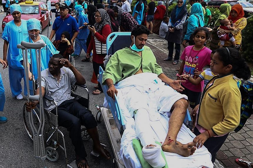 Sultanah Aminah Hospital medical staff evacuating patients after a second fire yesterday, caused by a spark at an electrical socket exposed to water. On Tuesday, six patients died in a blaze at the hospital.