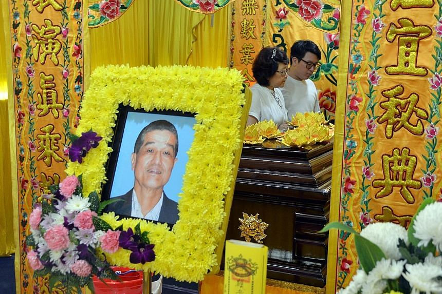 Mr Ong Peck Hock's wife Bessie and their son at his wake yesterday. The retiree, who had a history of heart attacks, collapsed in Serangoon Road on Sunday and was helped by Mr U. Silvakumar and other devotees on their way to a fire-walking ceremony.