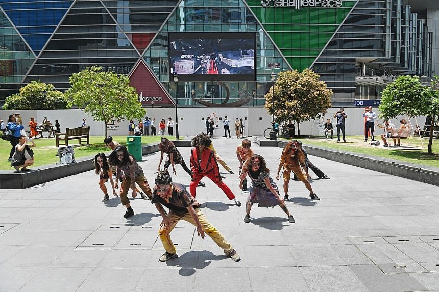 Under the blazing sun, a flash mob re-enacted Michael Jackson's 1983 horror-themed music video, Thriller, outside Raffles Place MRT station yesterday. Led by Mrs Crystal Wagar, wife of the United States Ambassador to Singapore Kirk Wagar, the group t
