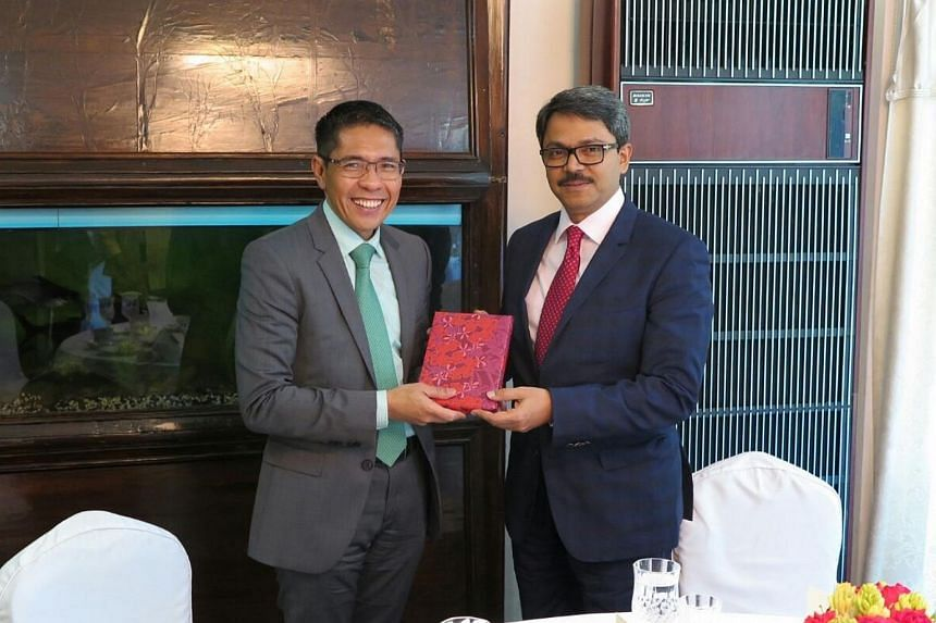 Senior Minister of State Maliki Osman presenting a gift to Bangladesh's State Minister for Foreign Affairs Md Shahriar Alam.
