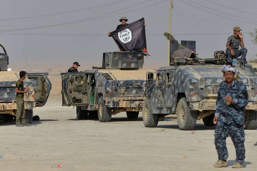 A member of federal police forces holds an ISIS flag during an operation against ISIS militants in the south of Mosul.
